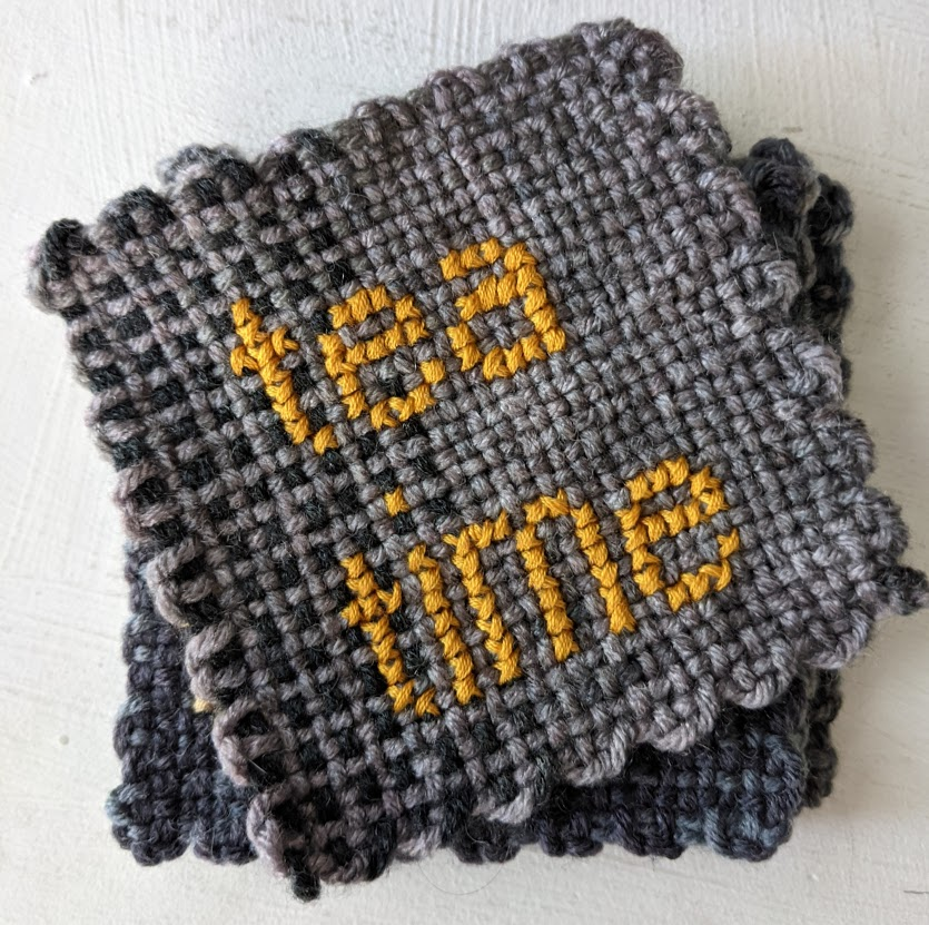 """stack of gray coasters. Top coaster is cross-stitched with the phrase """"tea time"""" in gold."""