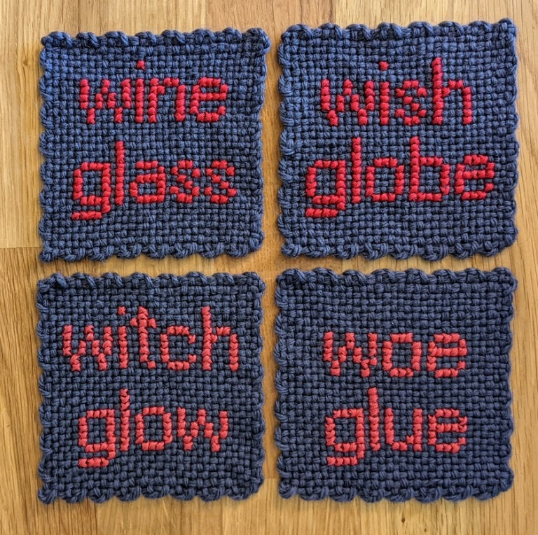 four purple coasters, sewn in hot pink with the following words: wine glass, wish globe, witch glow, woe glue